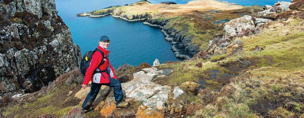 picture of a hiker walking along a ridge next to an inlet