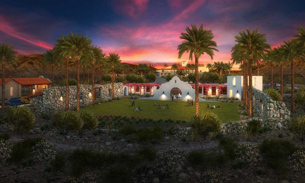 A high-end resort in the desert surrounded by palm trees at sunset.