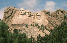 View of Mount Rushmore. The carved faces of the four historical figures, George Washington, Thomas Jefferson, Theodore Roosevelt and Abraham Lincoln are framed by a brilliant blue sky and puffy white clouds. Bright green coniferous trees in the foreground provide contrast to the granite stone into which the faces are carved.