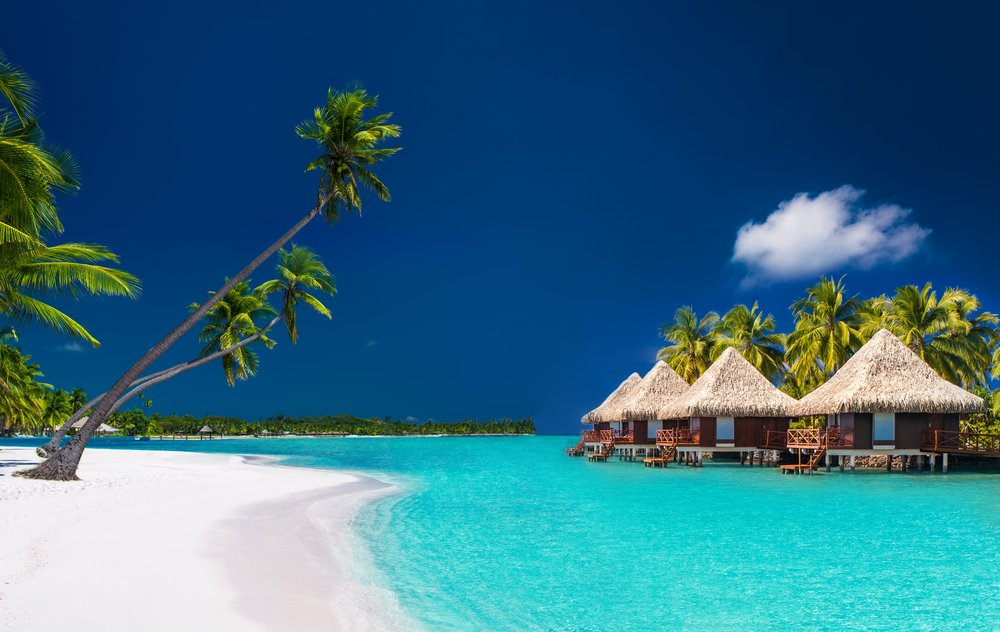 Whit sandy beach, palm trees, and three grass huts standing in turquoise water.
