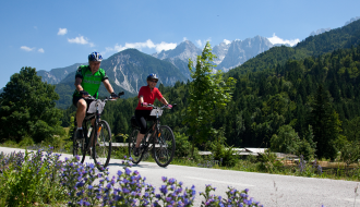 picture of two people biking with mountains in the distance