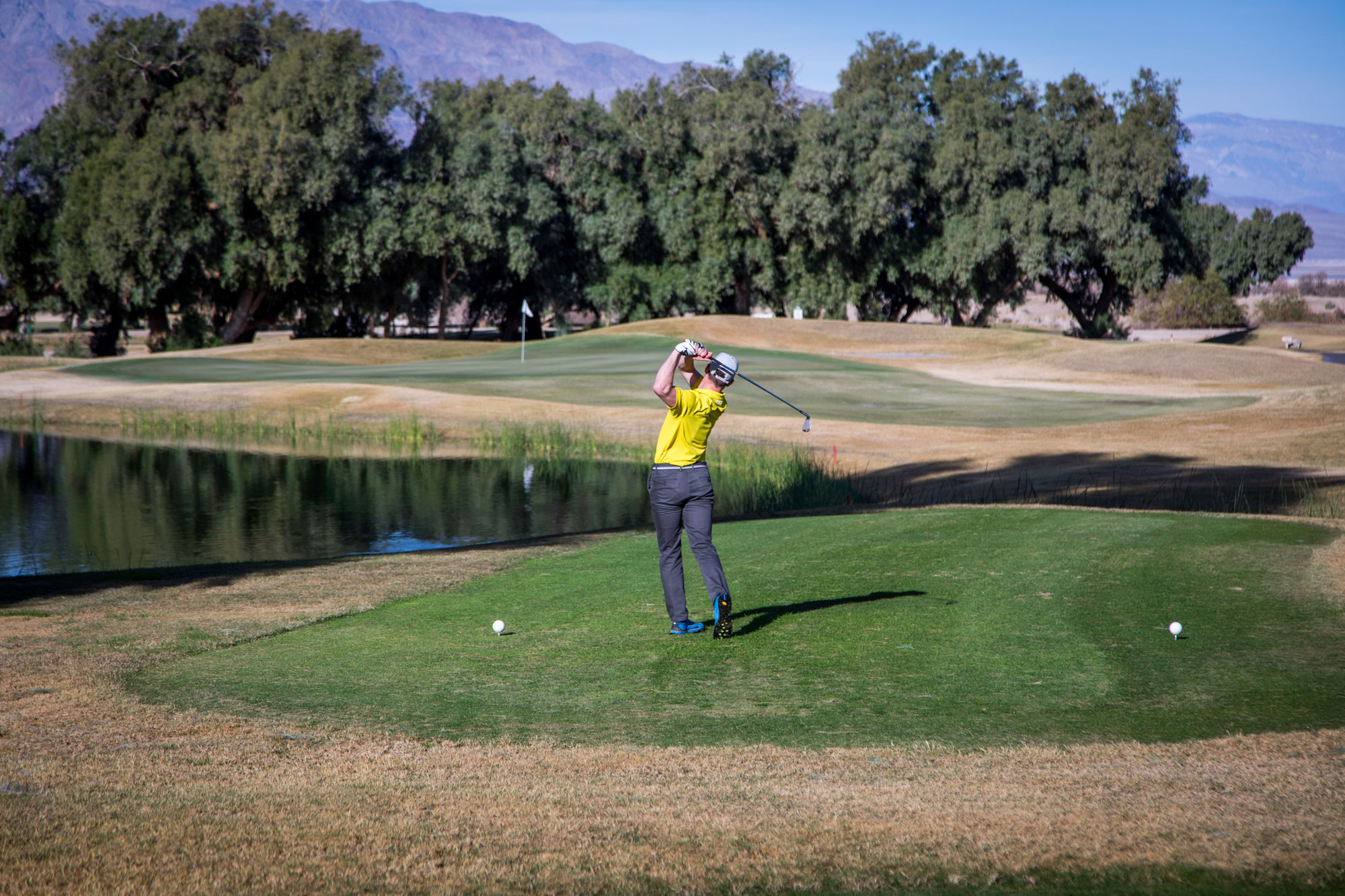 A man swings his club on a golf course.