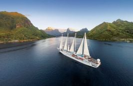 An aerial shot of a Windstar cruise ship sailing with full masts