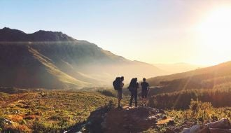 three hikers stand on a hill at sunset