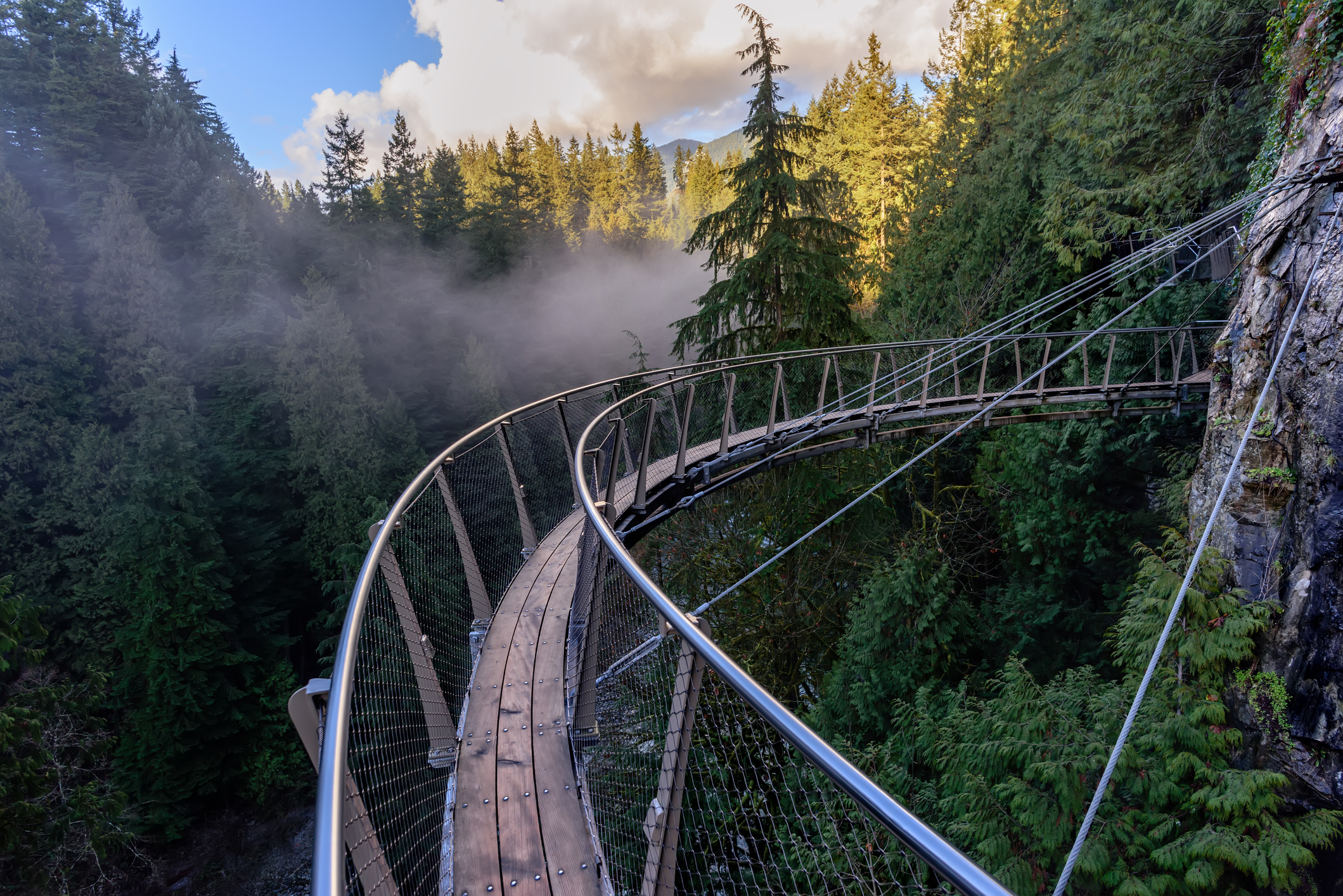 a view from above from the suspension bridge on rough streams of a mountain river among green forests white fog and rocky mountains in a sunny, summer day