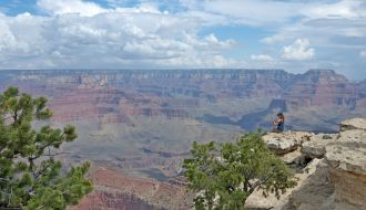 Grand Canyon South Rim, girl sitting on the edge of cliff with nice clouds above in Arizona